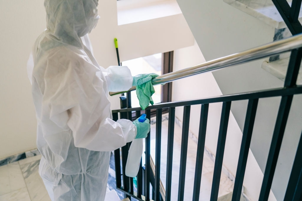 A person wearing a mask, gloves and a safety suit